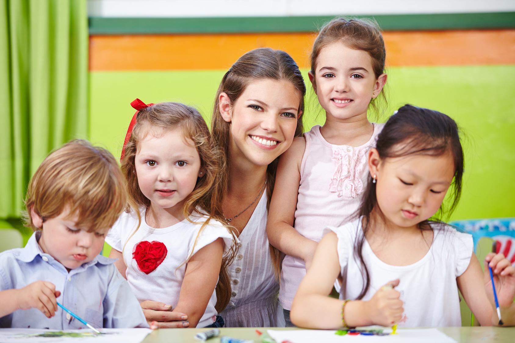 Lächelnder Erzieher und glückliche Kinder im Kindergarten malen