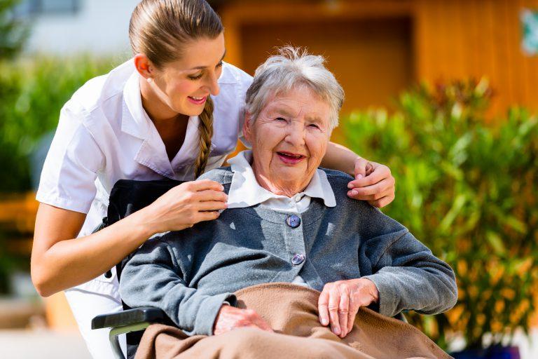 Senior woman in nursing home with nurse in garden sitting in wheelchair